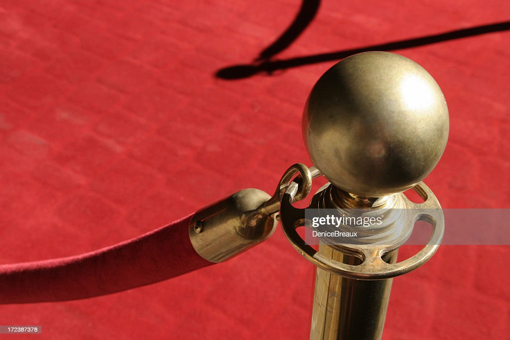 Close-up of gold stanchion holding red rope over red carpet : Stock Photo