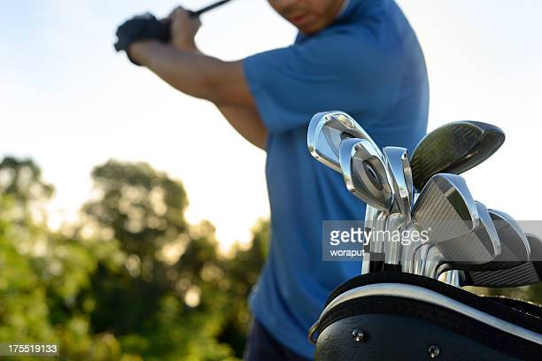 Close-up of golfer practicing swing with a bag of golf clubs