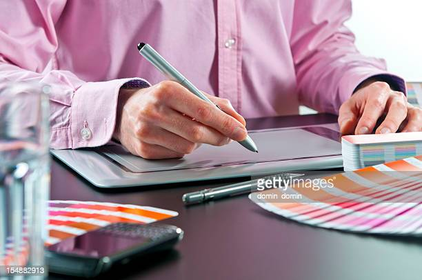 Close-up of graphic designer working on digital tablet, colour swatches