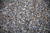 Close-up of gray stones of different sizes on the floor in the old town, background