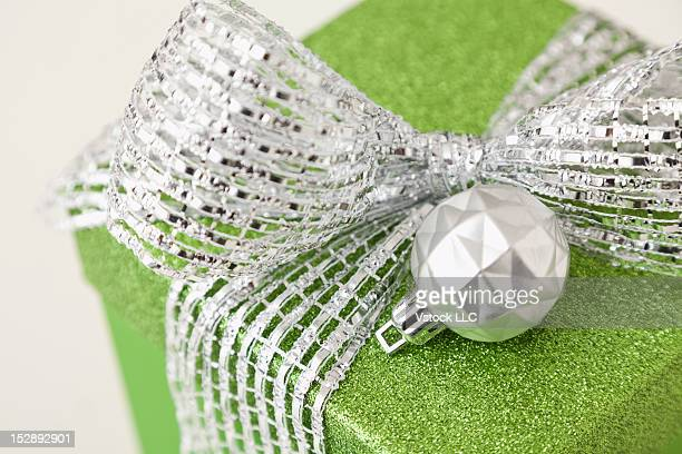 Close-up of green gift with christmas bulb