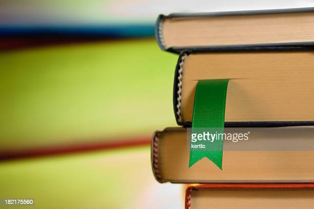 Close-up of green ribbon bookmark in a stack of books
