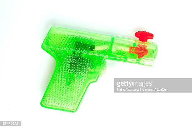 Close-Up Of Green Squirt Gun Against White Background