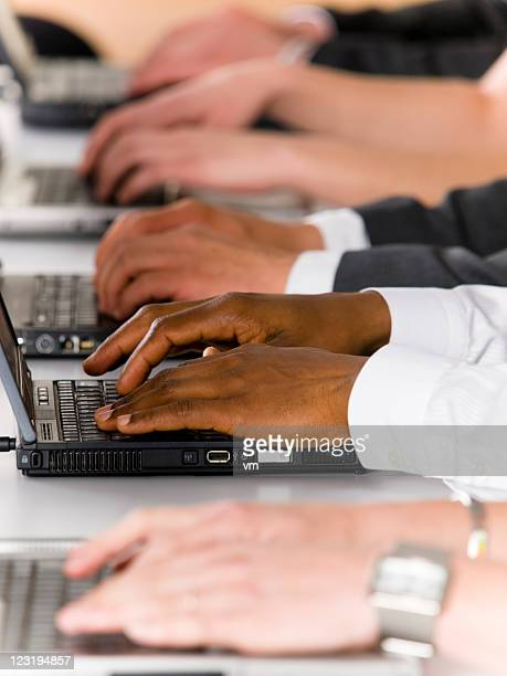 Closeup of group with human hands operating laptop