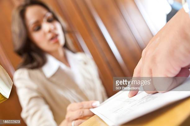 Closeup of guest pointing to hotel bill at front desk