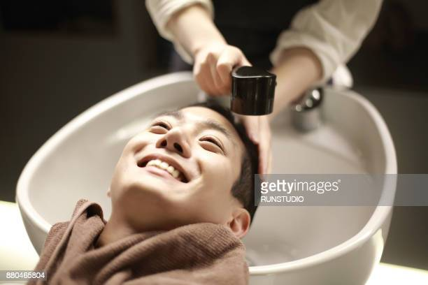 Close-up of hairdresser's hand washing man's hair