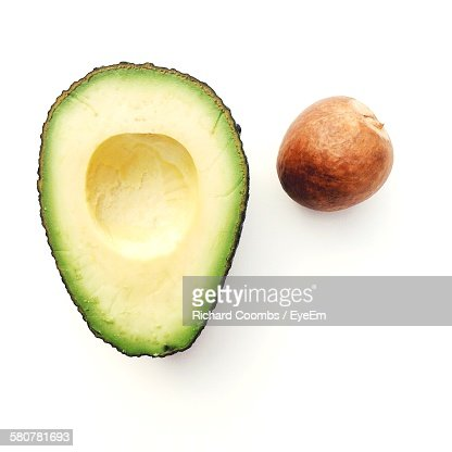 Close-Up Of Halved Avocado With Seed Against White Background