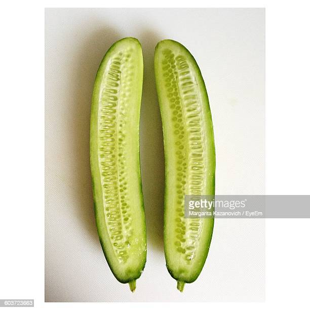 Close-Up Of Halved Cucumbers Against White Background