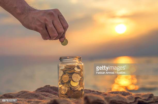 Close-Up Of Hand Collecting Money In Jar At Beach