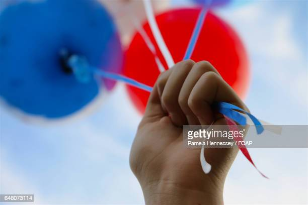 Close-Up Of Hand Holding Balloons