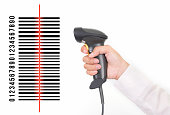 closeup of hand holding bar code scanner and scanning code on white background