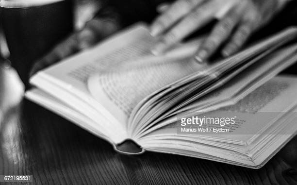 Close-Up Of Hand Holding Book At Table