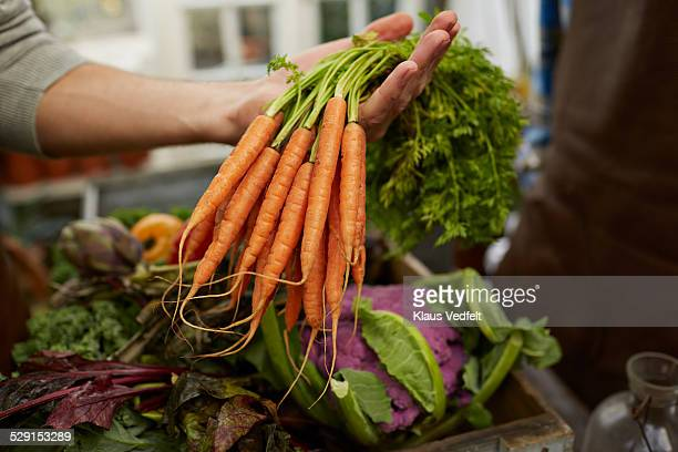 Close-up of hand holding bundle of carrots