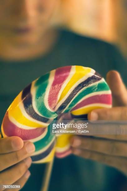 Close-Up Of Hand Holding Colorful Lollipop