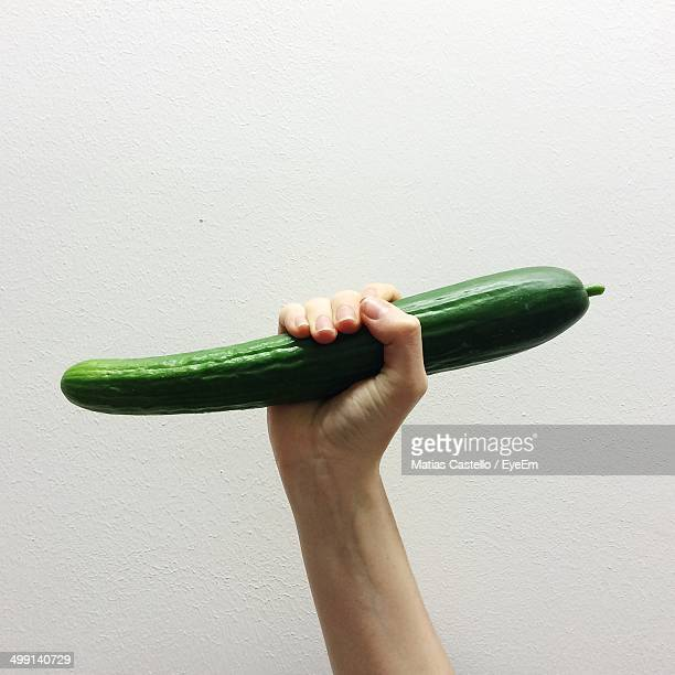 Close-up of hand holding cucumber over white background