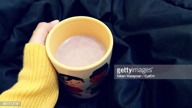 Close-Up Of Hand Holding Cup Of Chocolate Milk