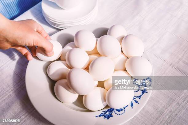 Close-Up Of Hand Holding Eggs In Plate