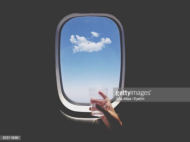 Close-Up Of Hand Holding Glass Of Water In Front Of Airplane Window