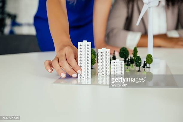 Close-up of hand holding high-rise building model next to wind turbine model on conference table