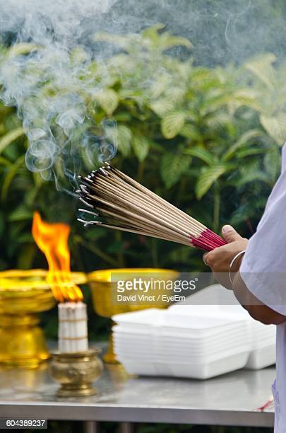 Close-Up Of Hand Holding Incense Sticks