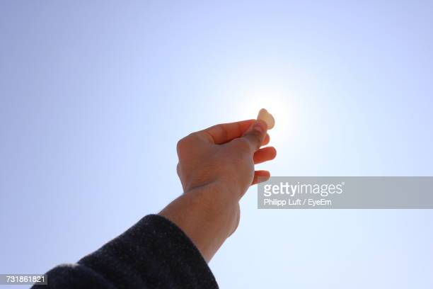 Close-Up Of Hand Holding Pebble Against Clear Sky