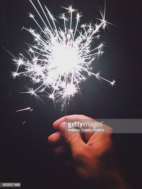 Close-up of hand holding sparklers at night