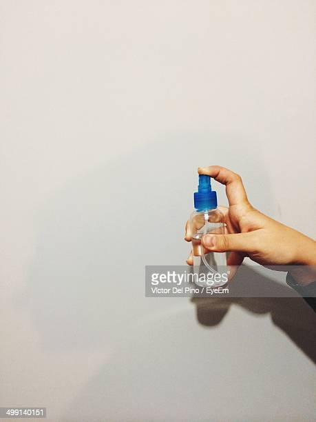 Close-up of hand holding spray bottle against wall