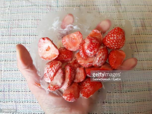 Close-Up Of Hand Holding Strawberries In Bowl Over Tablecloth