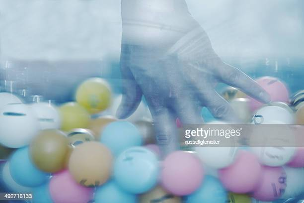 Close-up of hand picking lottery ball from glass bowl