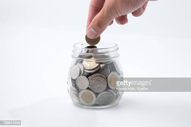Close-Up Of Hand Putting Coin Into Jar Against White Background