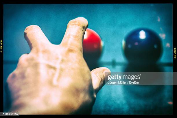 Close-up Of Hand Reaching Towards Pool Balls