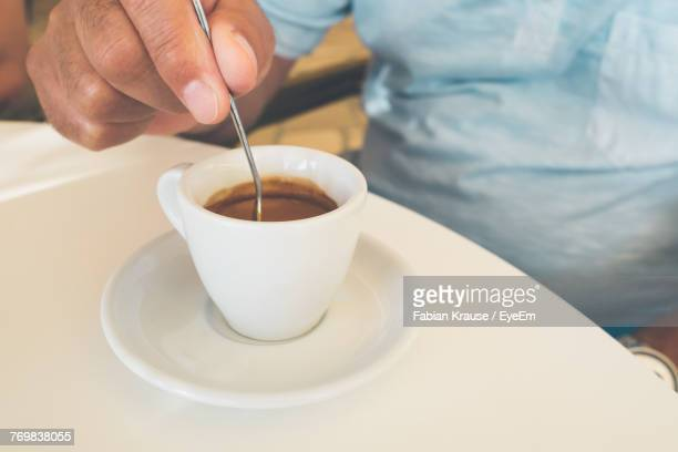 Close-Up Of Hand Stirring Coffee In Cup