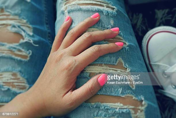 Close-Up Of Hand Touching Ripped Jeans
