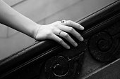 Close-up of hand with finger rings on wooden rail