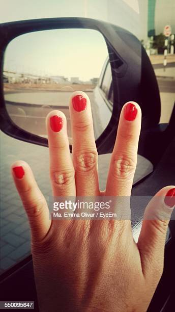 Close-Up Of Hand With Red Nail Polish In Car