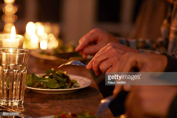 Close-up of hands at candlelight dinner