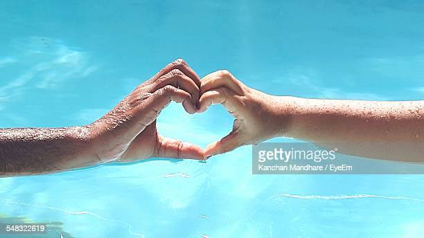 Close-Up Of Hands Forming Heart Shape Against Blue Water