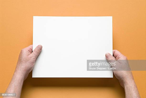Close-Up Of Hands Holding Blank Paper