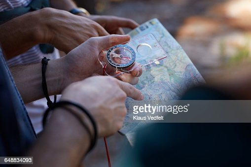 Close-up of hands holding compass & map