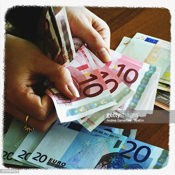 Close-up of hands holding Euro notes
