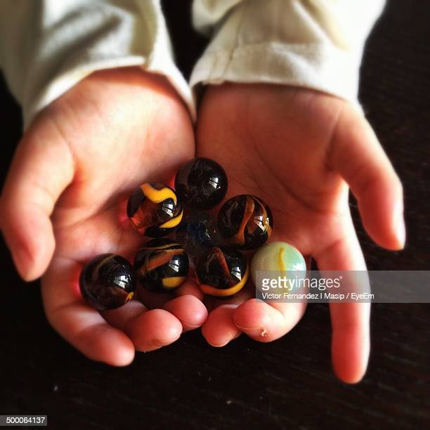 Close-up of hands holding marbles over black background