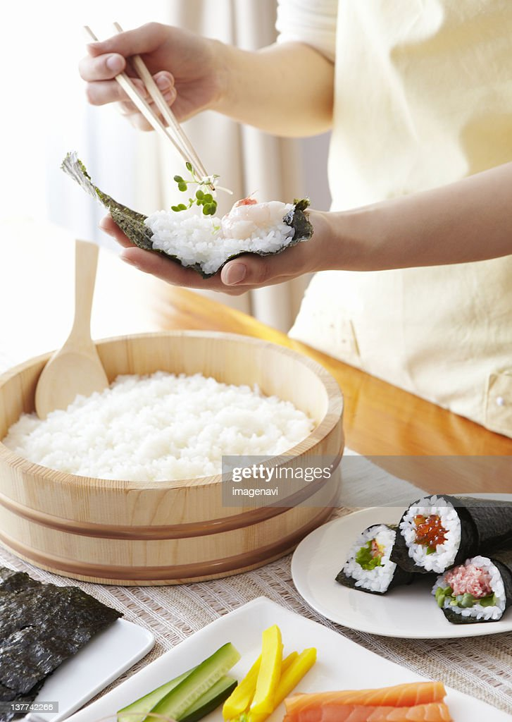 Closeup of hands making hand-rolled sushi