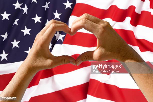 Close-Up Of Hands Making Heart Shape Against American Flag