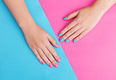 Closeup of hands of a young woman with manicure on nails against pink background