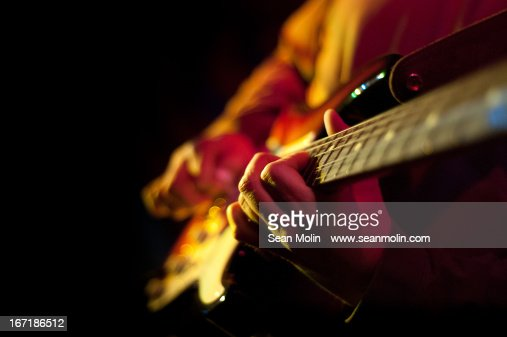 Closeup of hands playing electric guitar
