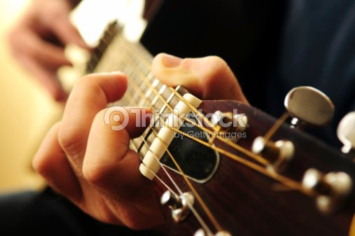Closeup Of Hands Playing Guitar Chords On Frets Stock Photo | Thinkstock
