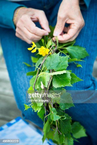 Close-up of hands preparing wreath of flowers, Nykoping, Sodermanland, Sweden