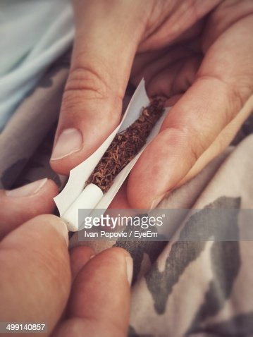 Close-up of hands rolling a joint