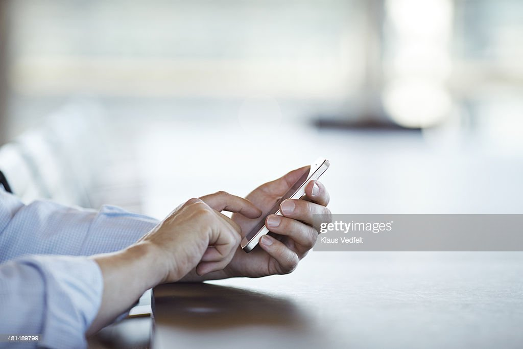 Close-up of hands scrolling on phone, side view.