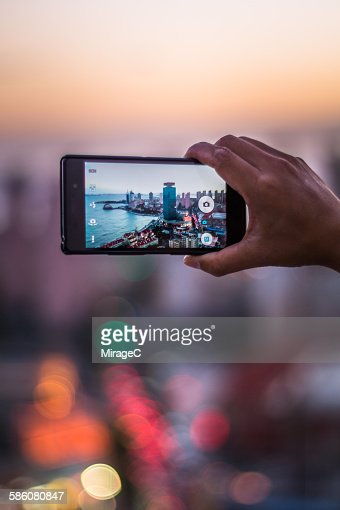 Close-up of hands taking picture of city skyline